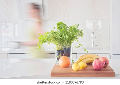 A woman quickly cooking healthy vegetarian food with kettle. Fruits on a clean table, granate apple, lemons, grape fruit, bananas, all white kitchen interior with herbs, coriander, parsley and salad