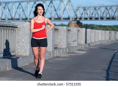 Woman race walking at the embankment