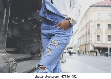 Woman in ragged blue denim overall posing on the city streets. Stylish girl in trendy overall, spring casual fashion look.