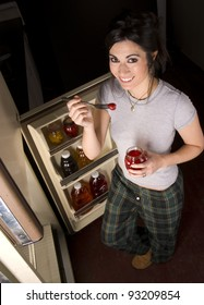 A woman raids the refrigerator late at night finding a fruit snack