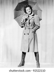 Woman in rain gear holding an umbrella and smiling