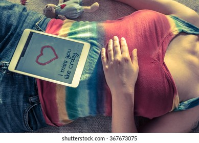 Woman in rainbow tank top lying on the floor with a tablet and teddy bear, missing her sweetheart - torso, high angle view.