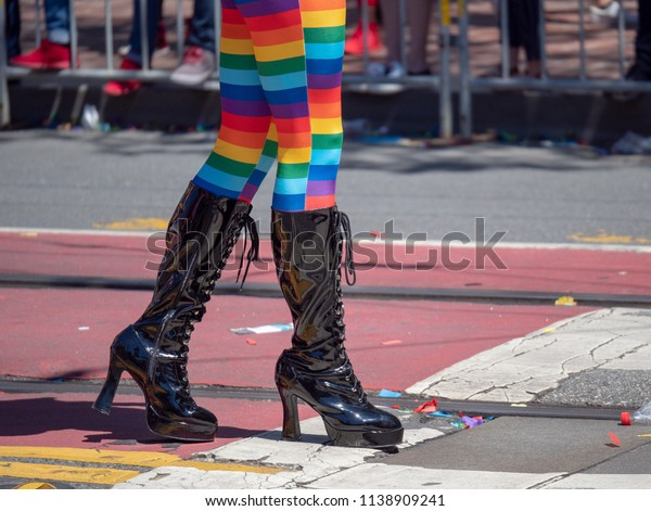 A woman with rainbow tights and high latex boots walking along a street