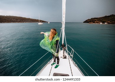Woman in raincoat is on the feed of yacht. Storm in the sea