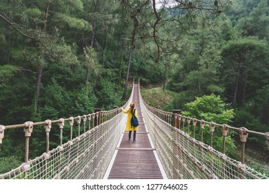 Woman with raincoat standing on suspension bridge