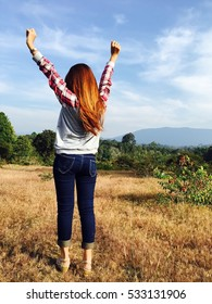 Woman raise her hands and standing to see mountain and sky