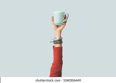 Woman raised arm up holding coffee cup