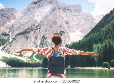 Woman with raised arms up looking at Braies Lake with mountains on background. Girl enjoying stunning view of Lago di Braies in Dolomites, South Tyrol, Italy, Europe. Beauty of nature image.