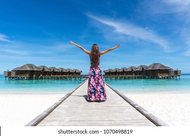 Woman with raised hands on bridge on beach in Maldives