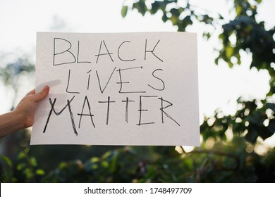 """Woman raised hands showing sign """"black lives matter"""". No rasicm. End rasicm. Against the background of trees and sunlight."""