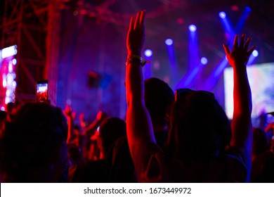 woman raised her hands up at a concert, dancing, lit by bright light at the festival at night