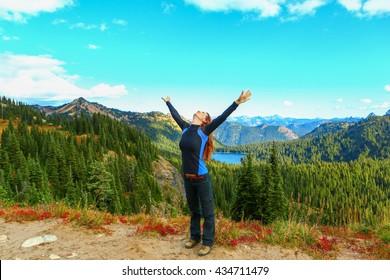 The woman raised her hands up, happy. Mount Rainier national park, Washington