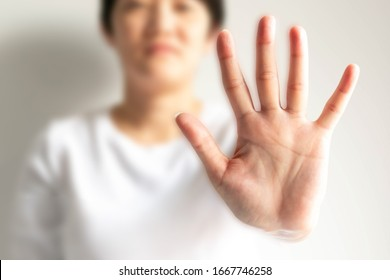 A woman raises an arm and showing a palm with five fingers; it is hand signs or body language in the meaning of please stop; say no; or forbid; on a white background, selected focus only at the palm.