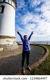 Woman raises her hands in a joyful moment next to North head lighthouse in Ilwaco, Washington.