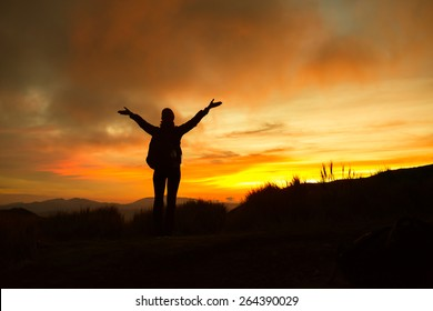 Woman raising her arms and enjoying the beautiful sunset