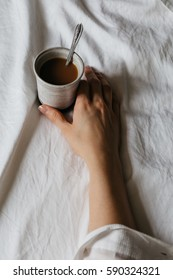 Woman Reaching for Cup of Coffee on Bed