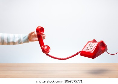 Woman reaching the red phone, urgent call waiting , classic red telephone receiver in hand, Vintage telephone on white background, flying in weightlessness with wooden desktop.