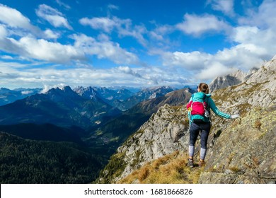 A woman reaching the top of Monte Coglians, Hohe Warte on the Austrian-Italian Alpine border. Very steep and narrow pathway that she walks on. She is not giving up, visible goal. Stunning view