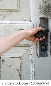 woman reaching up to turn the door knob on an old wooden rustic door