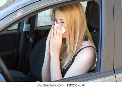 Woman reacts with pollen on hay fever in a car