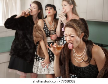Woman reacts to strong alcohol while friends smoke and drink in the kitchen