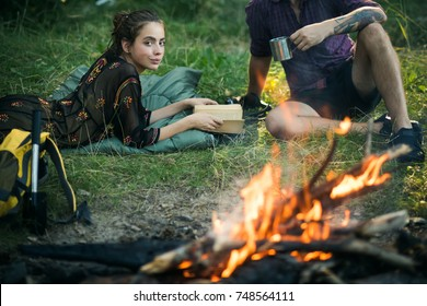 Woman read book and man with mug at campfire. Couple of hikers relax at bonfire on nature. Summer vacation concept. Camping, hiking, lifestyle.