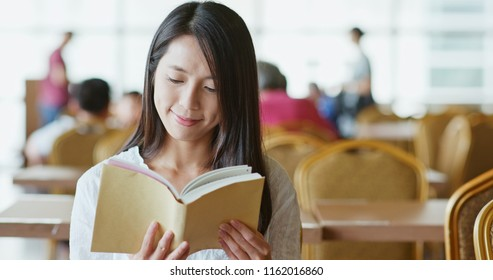 Woman read on book inside restaurant