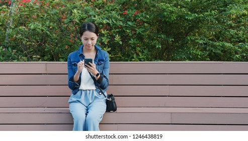 Woman read on smart phone and sit on the bench