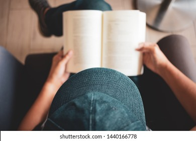 Woman read the pocket book on the armchair, top view or over head shot of woman wearing hat rest the book on her lap to read, shallow depth of field and focus at the hat