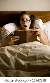 Woman reading in bed with a shocked expression