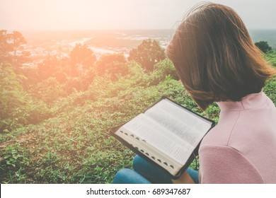 Woman Reading Bible on Mountain in the Morning with copy space