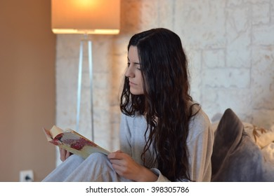 woman reading a book in bed happily in the morning