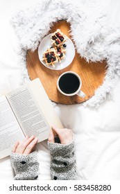 Woman reading a book in bed and having breakfast