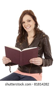 A woman reading a book with a big smile on her face.