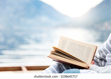 Woman is reading book by winter sea, mountains, beach. Cozy picnic on wooden pier with warm plaid. Girl is enjoying life, relaxation, wellbeing.