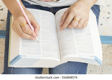 woman reading a book dictionary english for study
