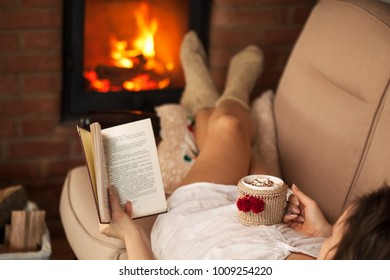 Woman reading a book and enjoying a hot chocolate by the fire - lying on the sofa, shallow depth