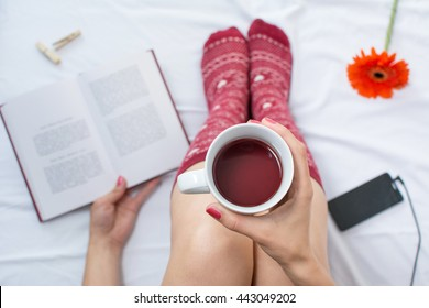 Woman reading a book and having cup of tea in bed