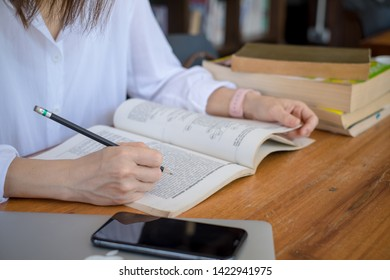 Woman reading a book in library. Portrait of college girl reading book in library, people, knowledge, education and school concept - happy student girl or young woman with book in library.