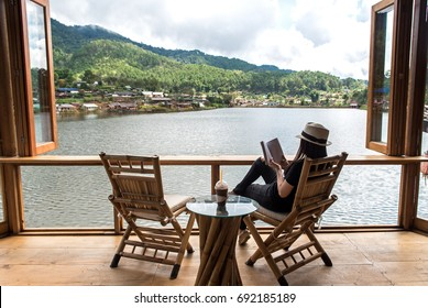 Woman reading a book lying and drink ice coffee on the chair in wood terrace against beautiful view relax and happy day, outdoor resort..  Lifestyle Concept