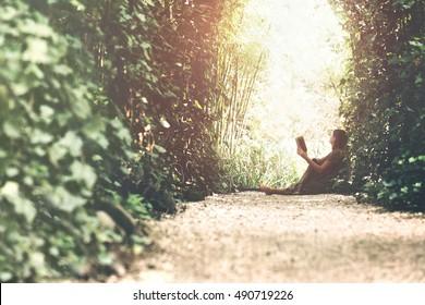 woman reading book in a magic garden