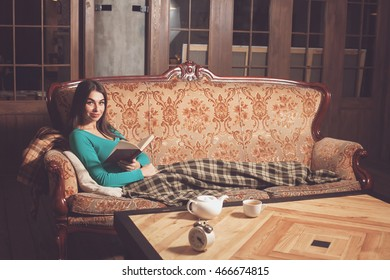 Woman is reading a book on the beautiful sofa with 
