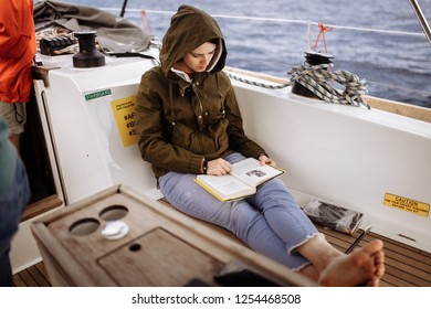 Woman is reading book on the boat. Literature break. Smart and clever girl