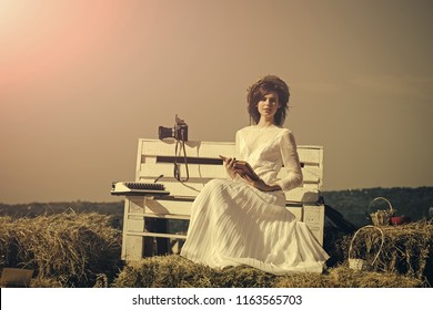 Woman reading book on grey sky, vintage filter. Girl sitting with typewriter and camera on bench. Lady in white dress and wreath on sunny day. Education and knowledge. Summer vacation concept.