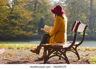 Woman reading a book on a park bench, leisure time in autumn park. fashion woman in yellow coat sitting on a bench.