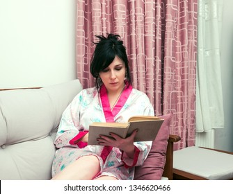 Woman reading a book on sofa at home