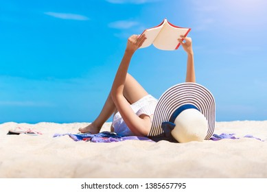 Woman reading a book on the tropical beach with relax on vacation time. Freedom travel concept.