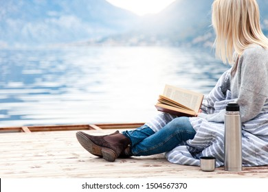 Woman is reading book on wooden pier by winter sea, mountains, beach. Cozy picnic with coffee, hot beverages, tea or cocoa in thermos, warm plaid. Girl is enjoying life, relaxation, wellbeing.