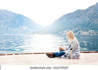 Woman is reading book on wooden pier by sea, mountains, beach. Cozy winter picnic with coffee, hot beverages or tea in thermos, warm plaid. Girl is enjoying life, relaxation, wellbeing.
