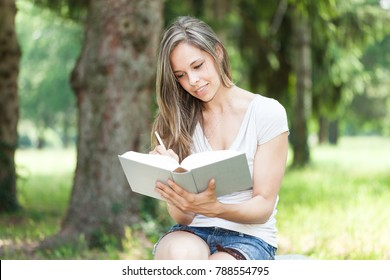 Woman reading a book at the park